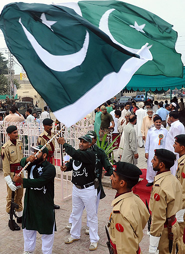 Pakistanis wave national flags during a ceremony to mark the country's Defence Day.