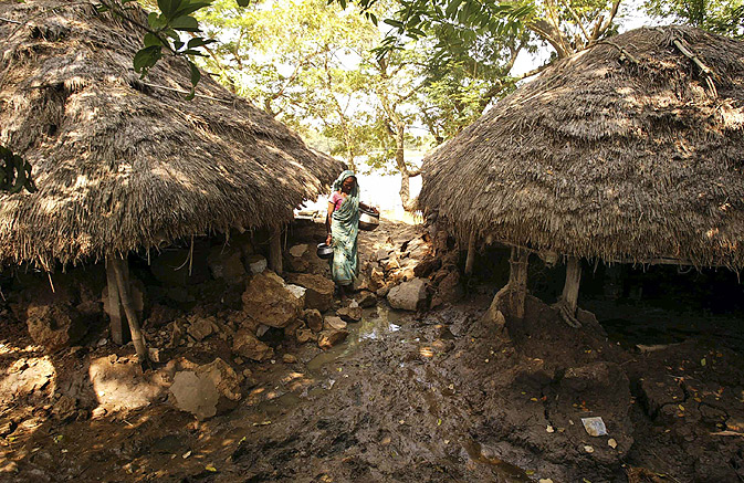 A villager walks past damaged homes near Rajnagar, in Kendrapada district, about 200 kilometers (125 miles) from Bhubaneshwar.
