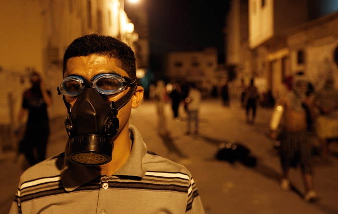 An anti-government protester wears a tear gas mask during a demonstration in the village of Karrana, west of Manama, September 1, 2011.