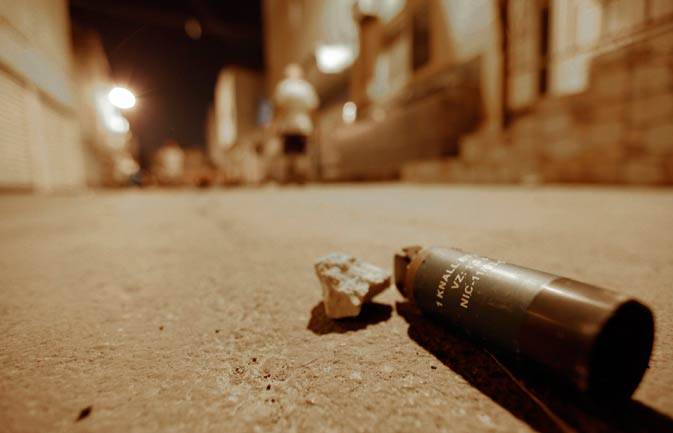 An unexploded percussion grenade fired by riot police is seen on the road.