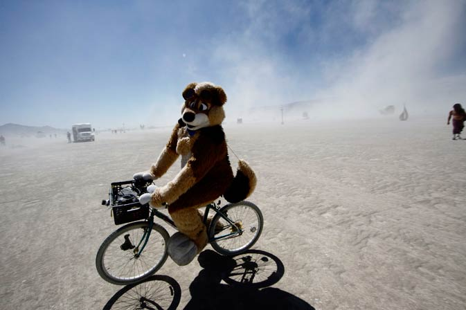 A participant dressed as a bear rides a bicycle.