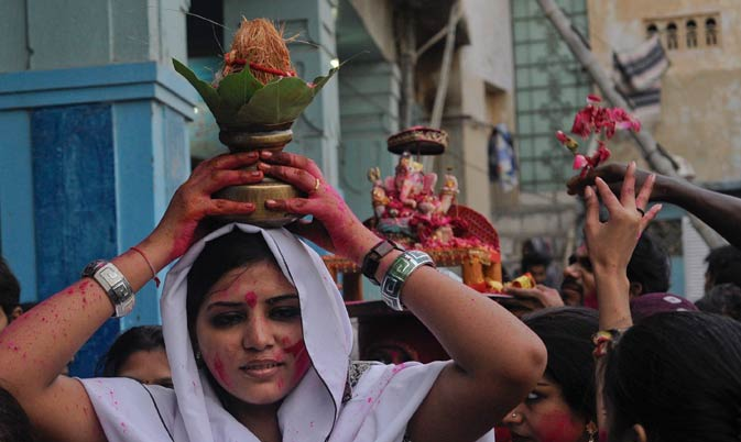 A woman carries a coconut on her head as an offering, with others.