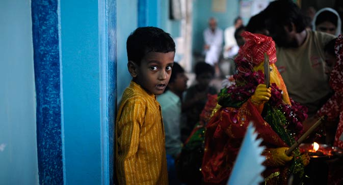A boy looks as he stands behind the idol of Ganesh.