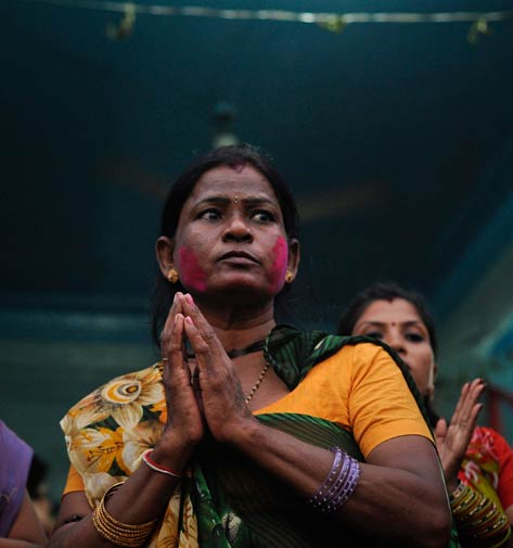 Champa, 45, has colour applied on her face as she prays with others.