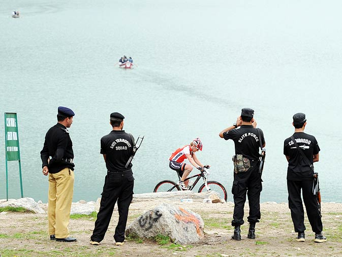 Pakistani policemen stand guard as local and international cyclists compete in the Himalayas 2011 International Mountainbike Race.
