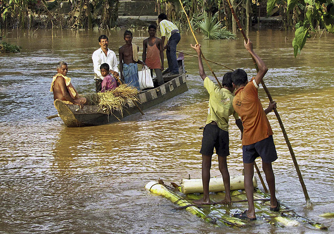 Village boys cross a flooded area on a makeshift raft in Jajpur district, in the eastern Indian state of Orissa.
