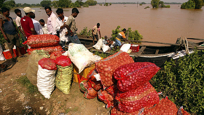 Flood affected villagers arrive at their marooned village on a country boat after floodwater receded at Danda Sahi village.