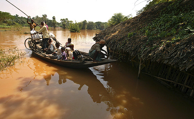 Villagers are ferried across what remains of their marooned villages after the floods.