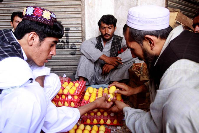 A customer, left, takes part in an egg fighting in Quetta, on Thursday, Sept 1, 2011. The egg tapping game or egg fight is a traditional  game in some parts of Pakistan and neighboring Afghanistan. The rule is to hold a hard-boiled egg and tap eggs of other participants to break them but to keep your own undamaged.