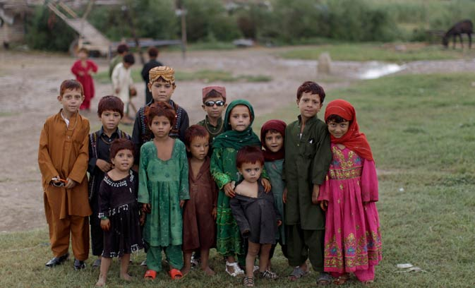 A group of Afghan refugee children pose for a picture while celebrating the second day of Eid, in a slum on the outskirts of Islamabad.
