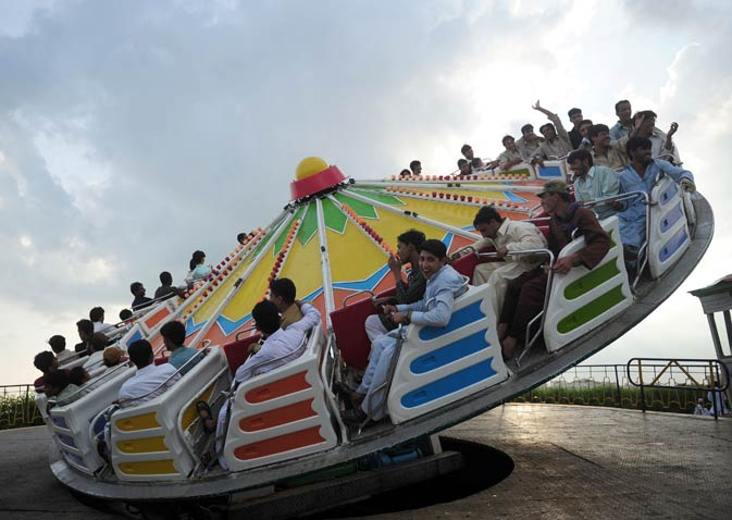 People at a fairground enjoy a ride to celebrate the second day of Eid in Karachi.