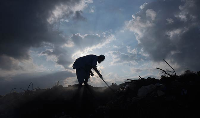 A man is silhouetted against the sun as he goes through a dumping ground for recyclable material in Karachi.