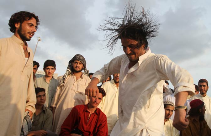 People watch a dance performance by a man who celebrates Eid in Karachi.