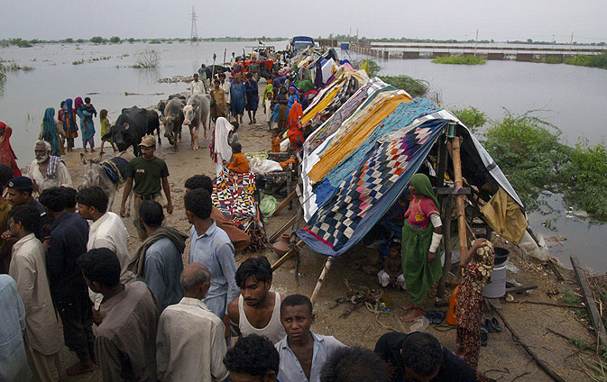 Displaced villagers take refuge on higher land after a flooding in Pangario.