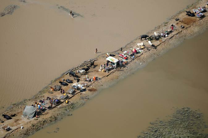 Flood affected villagers seeking refuge on a dry patch in the flood-hit Sanghar district of Sindh province on September 19, 2011.