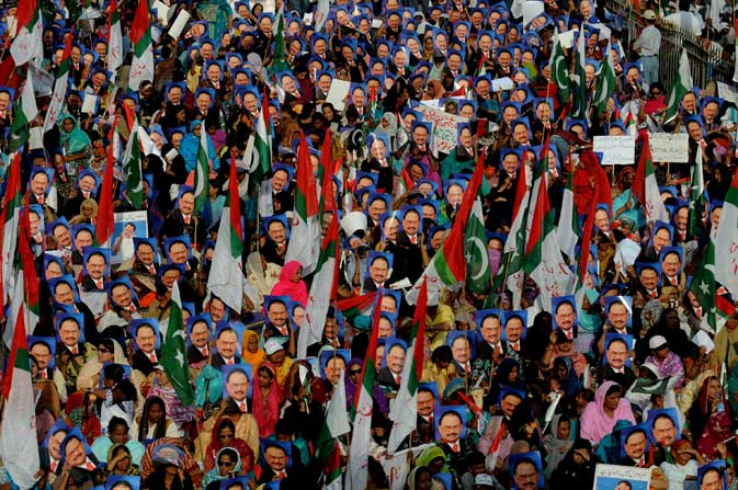 Activists of Muttahida Qaumi Movement (MQM) carry pictures of their party chief Altaf Hussain during a rally in Karachi on October 30, 2011, in a show of support for president Asif Ali Zardari.