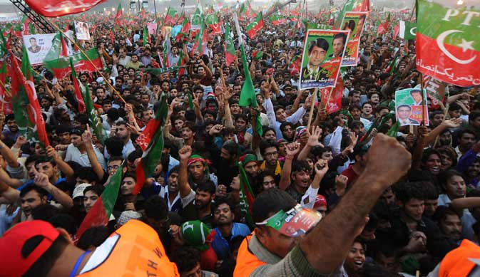 Supporters of Pakistani politician and former cricketer Imran Khan shout slogans during a rally in Lahore on October 30, 2011. A crowd of thousands gathered October 30, for a rally in the Pakistani city of Lahore called by Khan to press President Asif Ali Zardari to step down.