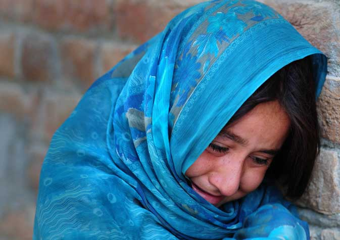Wajiha weeps as she talks to AFP during an interview outside her house in Tangi.