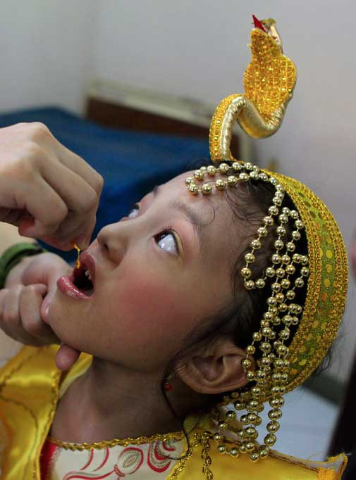 A girl in a Halloween costume receives Vitamin A drops during a medical mission conducted by a civic group as part of the U.N.'s countdown to the seven billion global population, in Tondo, Manila October 29, 2011 ? Reuters photo.