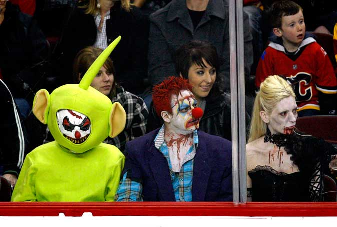 Hockey fans watch the game wearing Halloween costumes as the St. Louis Blues play the Calgary Flames in an NHL hockey game in Calgary, Alberta, Friday, Oct. 28, 2011 ? AP photo.