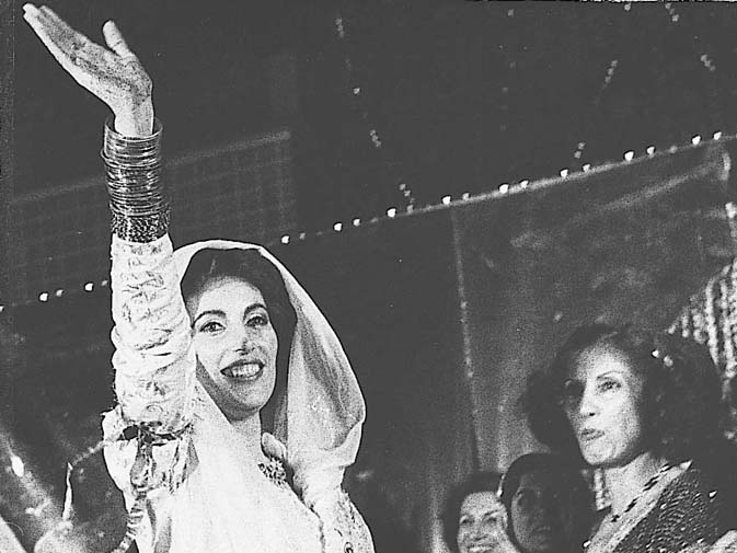 The list of tragedies that Begum Bhutto suffered is long. Her younger son, Shahnawaz, died in mysterious circumstances at his flat in southern France in 1985. Despite the trails and tribulations, some joyous moments awaited her. Here a happy Benazir Bhutto waves at the crowd at the People's Stadium in Lyari at her wedding. Seen in the background is Begum Bhutto. ? Dawn File Photo