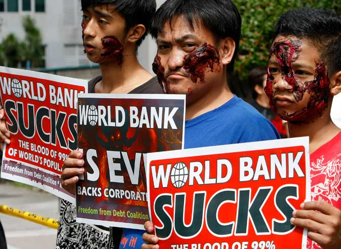 Protesters, sporting their Halloween costumes and make-up, display placards as they picket the World Bank office Thursday Oct.27, 2011 where visiting World Bank President Robert Zoellick is holding a news conference at suburban Mandaluyong, east of Manila, Philippines. Zoellick welcomed a deal clinched by European leaders to address their two-year debt crisis, saying it may have helped avert the spread of the financial turmoil to emerging markets that provide half of global economic growth ? AP photo.