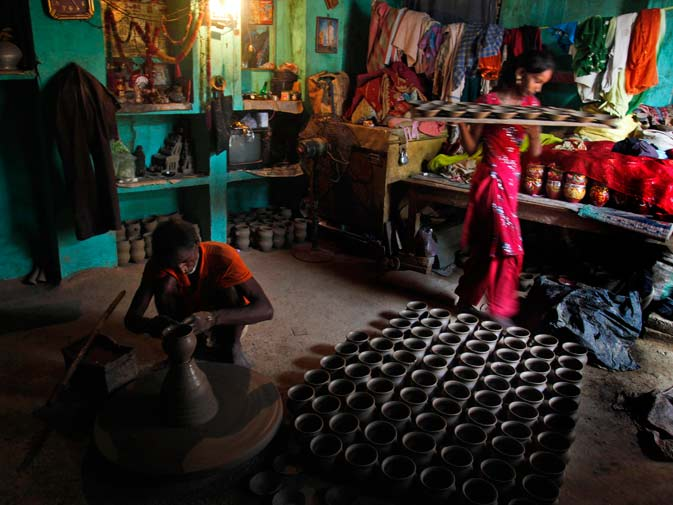A potter makes earthen lamps for the upcoming Diwali festival in Allahabad, India. ? AP