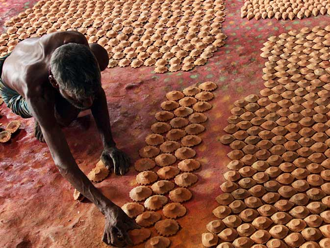 A labourer arranges earthen lamps ahead of Diwali in Kolkata, India. ? AP