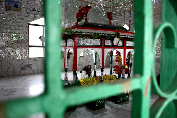 The view of the shrine of Sufi Pir Haji Syed Sakhi Sultan through a grill barricade surrounding the area.