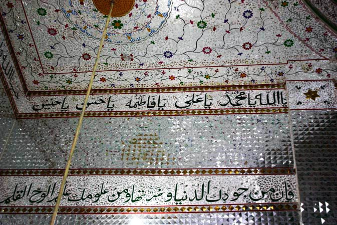 The walls embedded with glass with Quranic versus written on them at the shrine.
