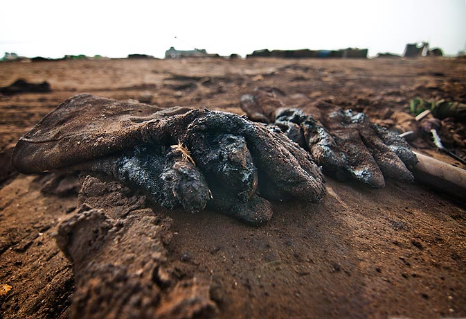 A pair of thick protective gloves lies on the sand covered in grease. In this particular ship 11 000 tons of grease were also present in the cargo.