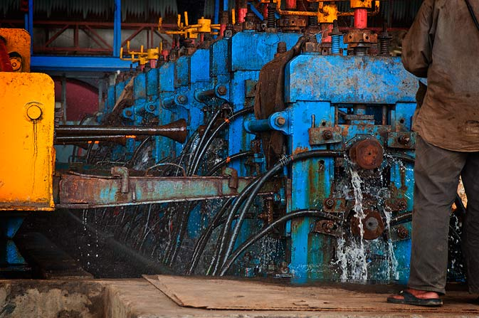 The process of making billets involves a complex mechanical, electrical, pneumatic and electronic system which is integrated to produce the reinforcement bars efficiently. Here water is being used to cool the finished product.
