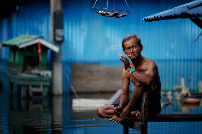 An elderly man smokes a cigarette outside his flooded home in a slum just outside Bangkok November 21, 2011.- Reuters Photo