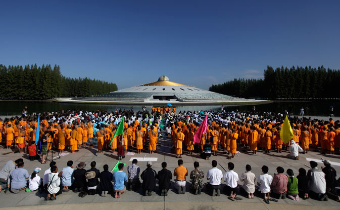 Thai Buddhist monks, city workers, volunteers and soldiers pray in front of Dhammakaya temple before starting a cleaning operation in Patum Thani on the outskirts of Bangkok, Thailand, Tuesday, Nov. 22, 2011.- AP Photo