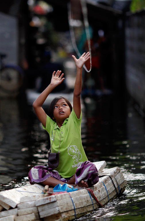 A girl tries to reach a rope to help her move through a flooded slum just outside Bangkok November 21, 2011. ? Reuters Photo