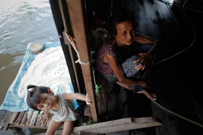 An elderly woman and her grandchild sit in their home which has been flooded for two months in Ayutthaya province November 19, 2011. ? Reuters Photo