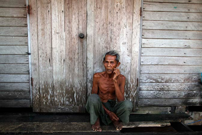 An elderly man sits outside his home which has been flooded for two months in Ayutthaya province November 19, 2011.- Reuters Photo