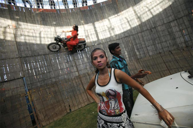 "Salma Pathan, 21, performs a motorcycle stunt inside the ""Well of Death"", one of the attractions at Ramlila fair, in the old quarters of Delhi September 29, 2011."