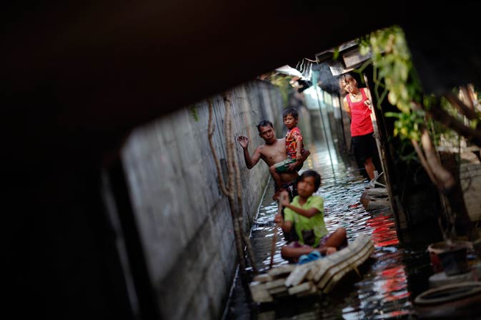 People make their way through a flooded slum just outside Bangkok November 21, 2011.- Reuters Photo