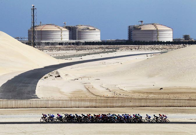 A pack of riders cycle past a chemical plant during the 5th stage of the 10th Tour of Qatar cycling race Sealine Beach Resort to Doha, February 11, 2011.