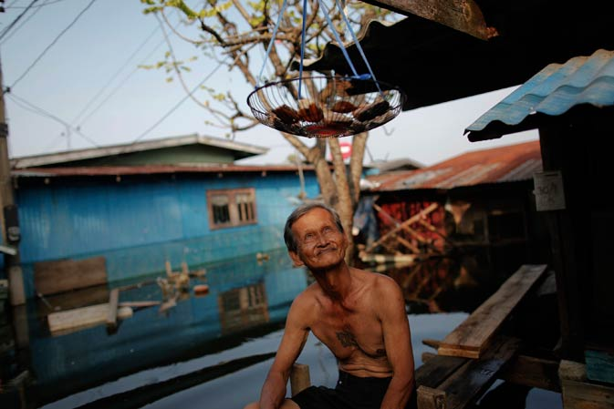 An elderly man looks at the fish being dried outside his flooded home in a slum just outside Bangkok November 21, 2011.-Reuters Photo