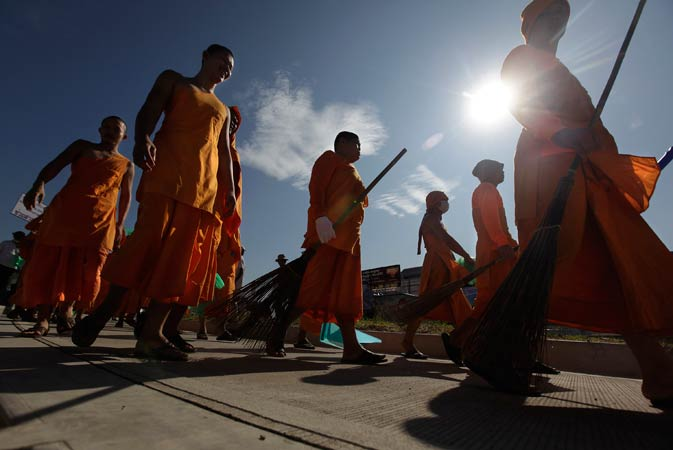 Thai Buddhist monks walk with their brooms during a cleaning operation in Patum Thani on the outskirts of Bangkok, Thailand, Tuesday, Nov. 22, 2011.-AP Photo