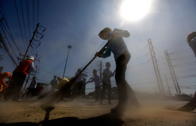 Thai volunteers sweep a road during a cleaning operation in Patum Thani on the outskirt  of Bangkok, Thailand, Tuesday, Nov. 22, 2011. ? AP Photo