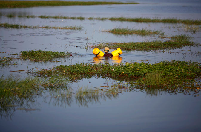 A man uses plastic canisters to float as he searches for lotus plants to use for food inflooded area in Ayutthaya province November 19, 2011. ? Reuters Photo