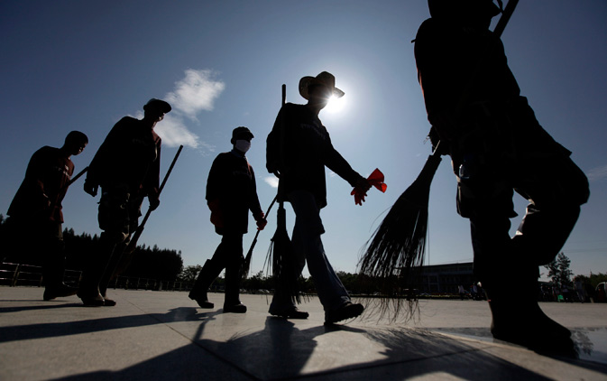 Thai soldiers are silhouetted as they walk with brooms during a cleaning operation in Patum Thani on the outskirts of Bangkok, Thailand, Tuesday, Nov. 22, 2011.- AFP Photo