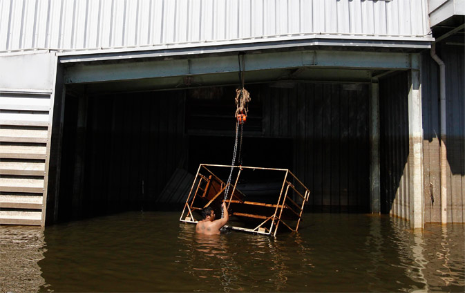 A worker works in his factory in a flooded area of Ayutthaya province November 22, 2011. - Reuters Photo