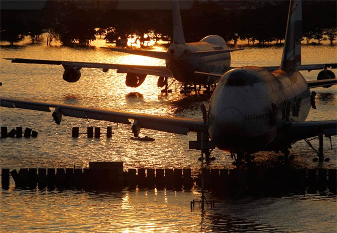 Airplanes are seen parked in flood waters at Bangkok's domestic Don Muang airport at dawn, November 20, 2011. ? Reuters Photo