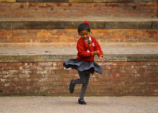 A girl in a school uniform plays at Bashantapur Durbar Square after school in Kathmandu.
