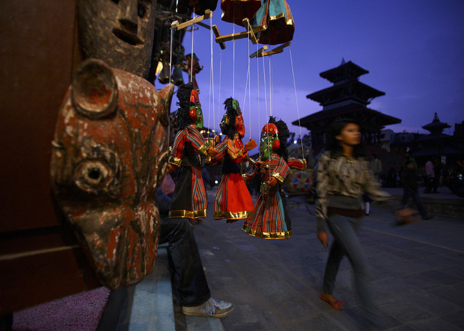 String-puppets hang in a mask shop as people pass by in the city of Bhaktapur.