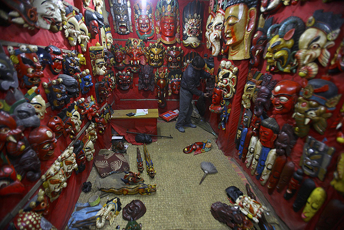 A shopkeeper arranges masks in his shop at the ancient city of Bhaktapur.